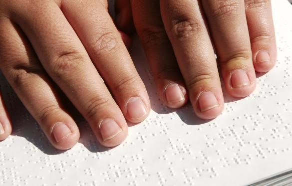 Fingers on a page reading Braille